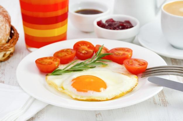 Spiegelei mit tomate und glas orangensaft
