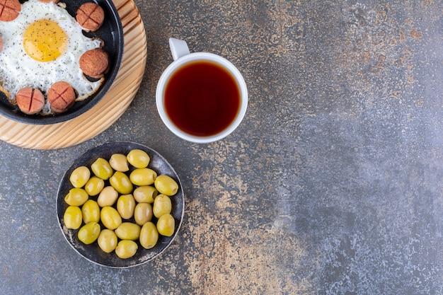 Spiegelei mit würstchen in einer schwarzen pfanne mit einer tasse tee