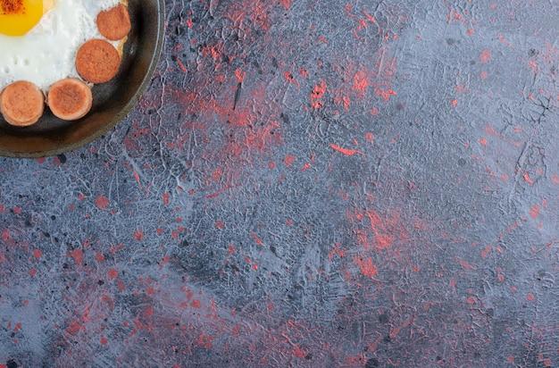 Spiegelei serviert mit gegrillter wurst und gewürzen auf einer holzplatte.