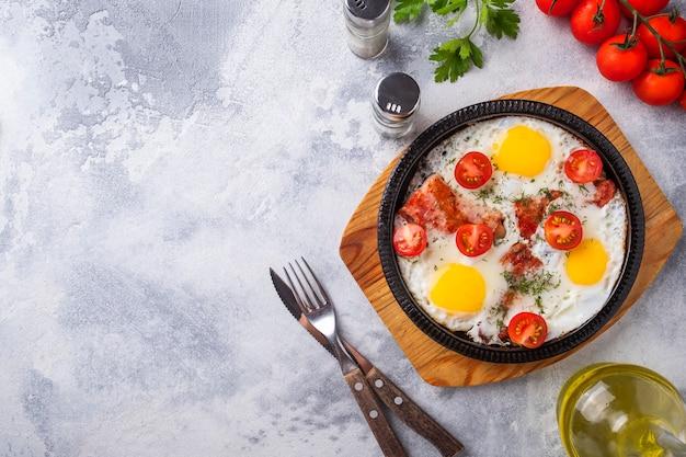Spiegeleier des geschmackvollen frühstücks auf einer bratpfanne. ansicht von oben.