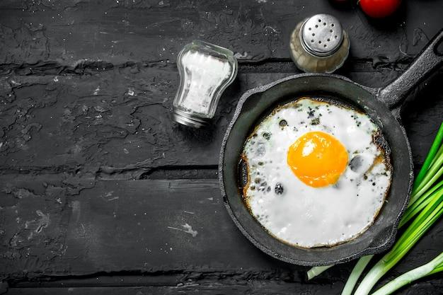 Spiegeleier in einer pfanne mit frühlingszwiebeln und tomaten. auf schwarzem rustikalem hintergrund.
