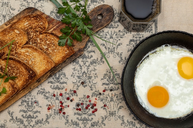 Spiegeleier in einer rustikalen eisenpfanne, toast auf einem holzbrett und eine tasse kaffee zum frühstück. draufsicht