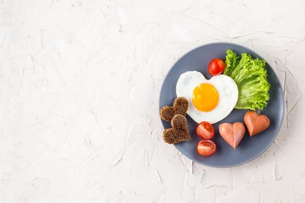 Spiegeleier in form eines herzens mit würstchen, kräutern und tomaten. frühstück für ihre lieben am valentinstag auf weißem hintergrund. draufsicht mit kopierraum