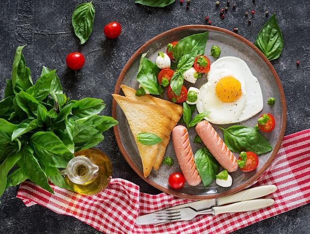 Spiegeleier in form von herz, wurst, toast und caprese-salat aus tomate, basilikum und mozzarella.