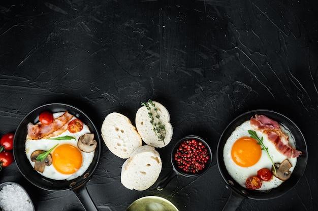 Spiegeleier mit kirschtomate und brot zum frühstück in der gusseisernen pfanne, auf schwarzem hintergrund, draufsicht flach, mit platz für textkopyspace