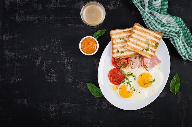 Spiegeleier mit schinken, tomaten und toast. leckeres englisches frühstück. brunch. draufsicht, überkopf