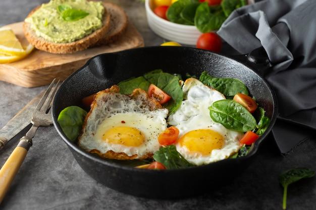 Spiegeleier mit spinat, avocado-toast und frischen tomaten, gesunde frühstücksnahrung,