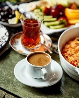 Spiegeleier mit tomaten und kräutern mit schwarzem tee und kaffee