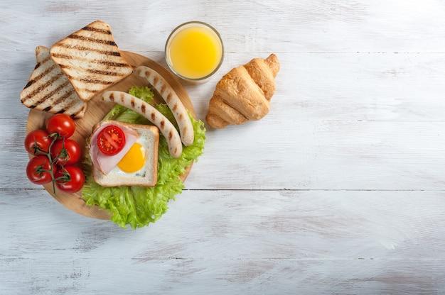 Spiegeleier mit würstchen und gemüse. frühstück mit orangensaft und croissant auf rustikalen holzbrettern.
