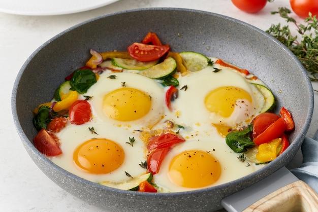 Spiegeleier pochiert mit gemüse auf teflonpfanne pfeffer tomaten spinat paprika zwiebel