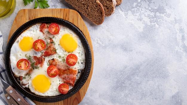 Spiegeleier, speck und gemüse des geschmackvollen frühstücks auf einer bratpfanne. ansicht von oben.