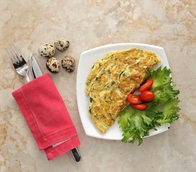 Spiegeleier von den wachteleiern mit spinat in einer hölzernen platte mit kopfsalat und tomaten