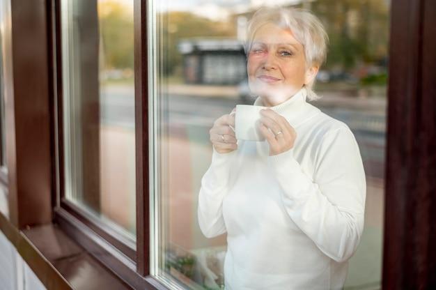 Spiegelung des älteren weiblichen trinkenden kaffees