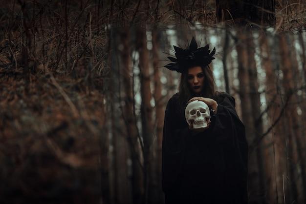 Spiegelung einer bösen gruseligen hexe mit dem schädel eines toten in einem spiegel in einem dunklen wald