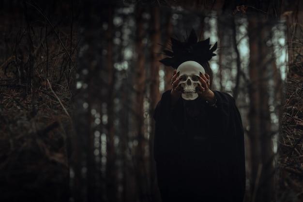 Spiegelung im spiegel einer bösen gruseligen hexe mit dem schädel eines toten, die in einem dunklen wald mystische okkulte rituale durchführt