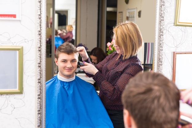 Spiegelung im spiegel eines lächelnden jungen mannes mit haarschnitt und gestylt von blonder stylistin im salon