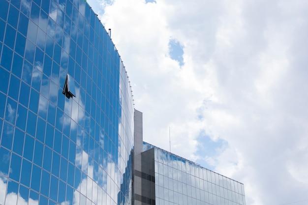Spiegelung von himmel und wolken in der hochhaus-spiegelfassade des gebäudes.