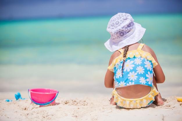 Spiel des kleinen mädchens mit strandspielwaren während der tropischen ferien