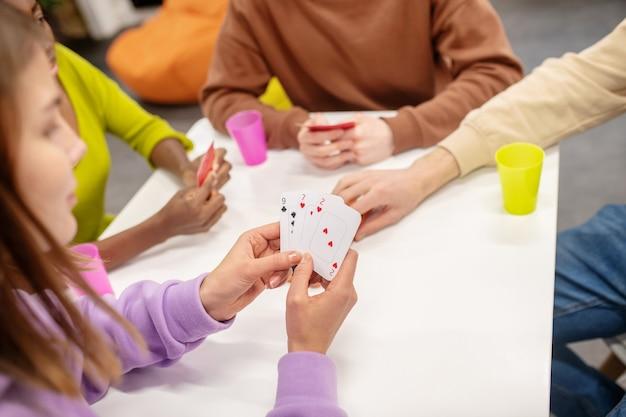 Spiel, prozess. junges mädchen, das ihre karten betrachtet, die am tisch mit ihren freundenspielern sitzen, die freizeit verbringen