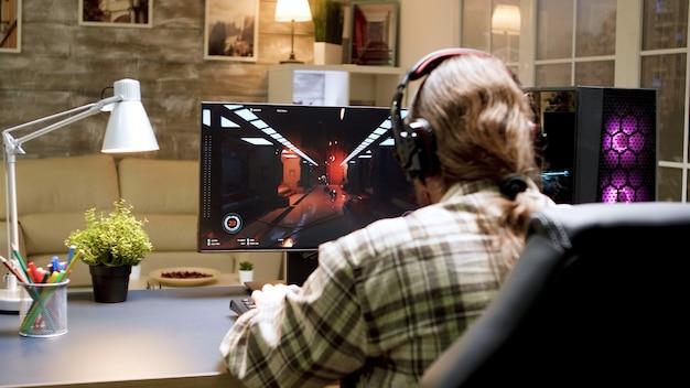 Spiel vorbei für einen mann mit langen haaren, während er shooter-spiele auf einem leistungsstarken computer spielt. frau mit vr-kopfhörer.