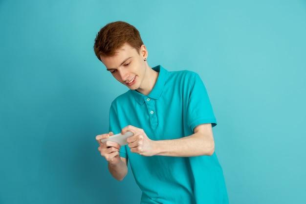 Spielen am telefon. das moderne porträt des kaukasischen jungen mannes lokalisiert auf blauer wand, monochrom. schönes männliches model. konzept der menschlichen emotionen, gesichtsausdruck,