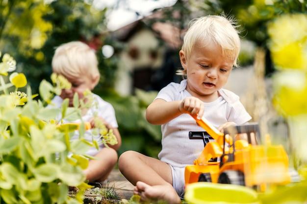 Spielen im garten mit einem plastikbaggerspiel. kleinkinder-zwillinge sitzen im hof und spielen mit pflanzen. ein kind mit blonden haaren und großen blauen augen sieht aus, als ob es mit seinem lieblingsspielzeug spielt