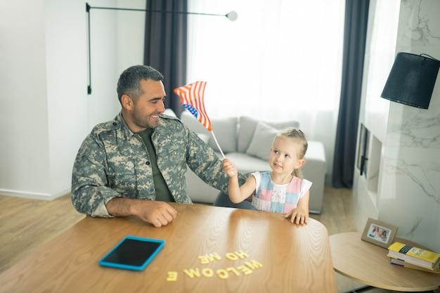 Spielen mit flagge. süßes dunkeläugiges mädchen, das mit der kleinen amerikanischen flagge spielt, während es papa zu hause trifft