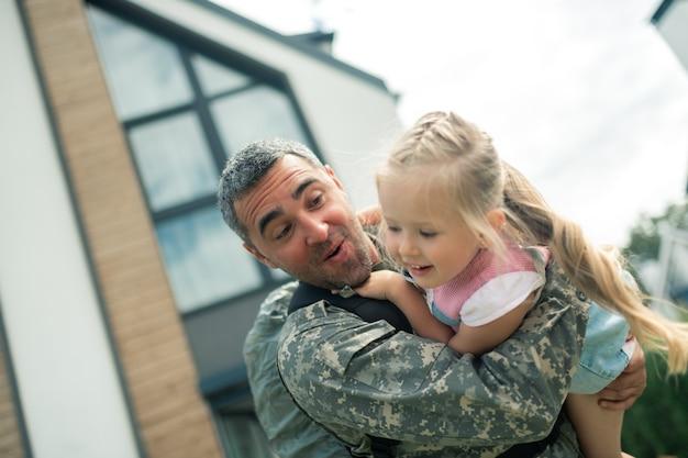 Spielen mit mädchen. bärtiger militäroffizier in uniform, der sich glücklich fühlt, mit seinem mädchen zu spielen