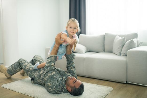 Spielen mit papa. kleine süße tochter fühlt sich großartig, wenn sie nach dem militärdienst endlich mit papa spielt playing