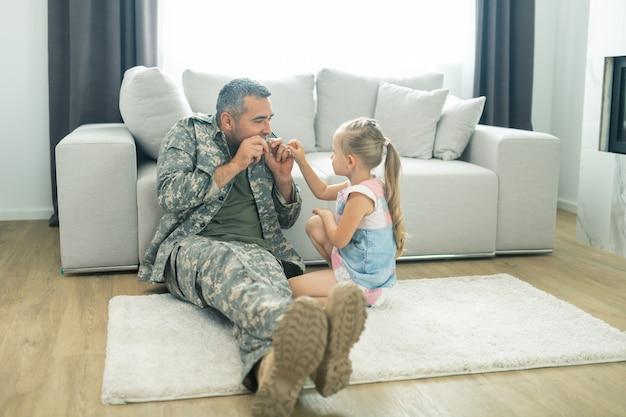 Spielen mit tochter. militäroffizier, der sich beim spielen mit der tochter im urlaub freut