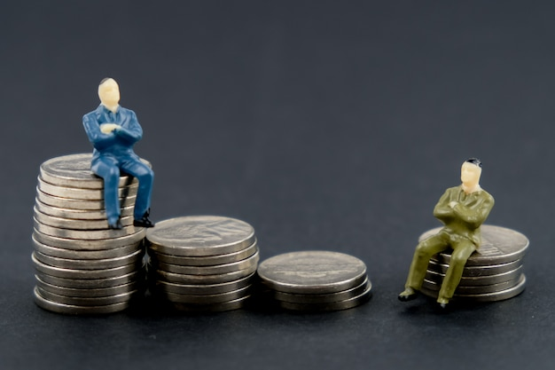 Spielen sie das modell des mannes sitzend auf einem stapel münzen auf einem schwarzen hintergrund.