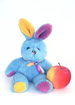 Spielen sie das weiche bunte kaninchen mit einem apfel