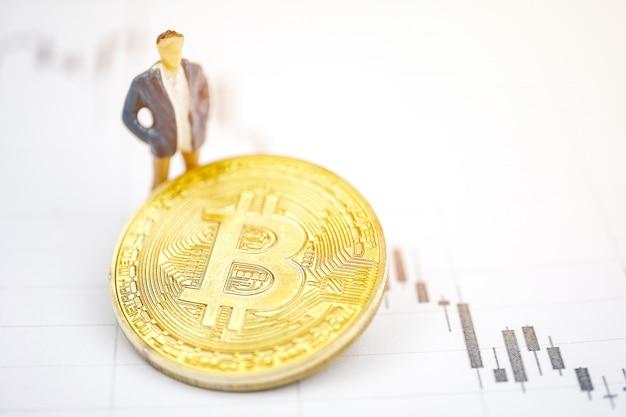 Spielen sie mannmodell nahe bitcoin münze auf dem hintergrund des diagramms.