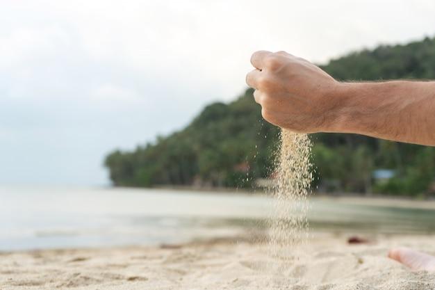 Spielen sie mit sand am strand. sand wird aus den händen vor dem hintergrund einer tropischen insel gegossen.