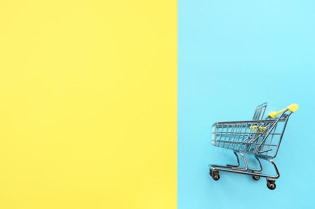 Spielen sie wagen für produkte auf einem zwei farbgelb-blauhintergrund.
