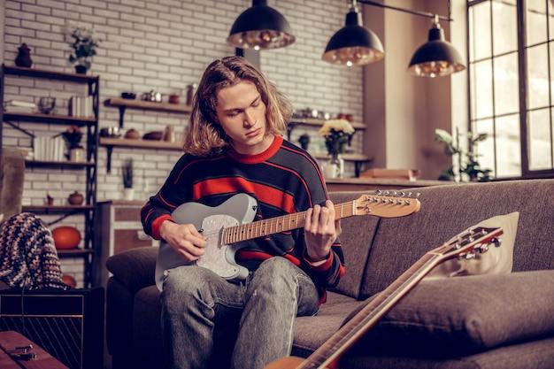 Spielen und komponieren. junge studentin in jeans und pullover spielt gitarre und komponiert melodiemelo