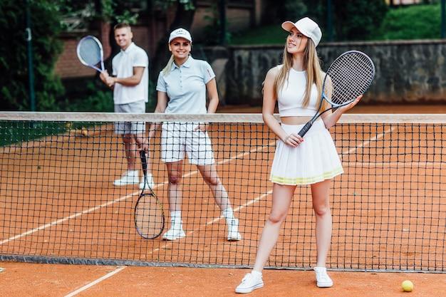 Spielen wir dieses spiel ... schöne junge frau, die tennis auf dem tennisplatz spielt.