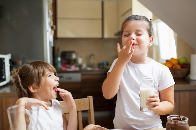 Spielende smileyschwestern beim frühstücken