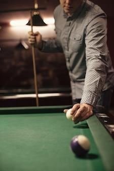 Spieler der amerikanischen billardpoule mit weißer kugel und stichwort
