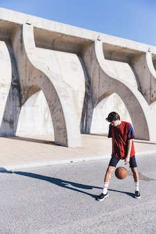 Spieler, der basketball auf straße übt