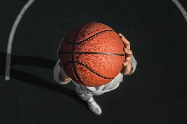 Spieler, der draufsicht des basketballs hält