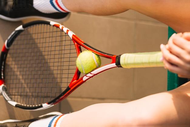 Spieler, der einen tennisschläger mit einem ball in ihm hält
