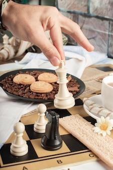 Spieler, der schach auf einem gebäcktisch spielt