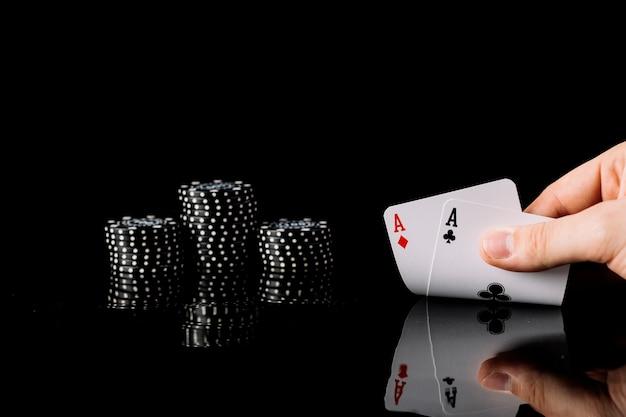 Spieler, der zwei spielkarten der asse nahe chips auf schwarzem hintergrund hält