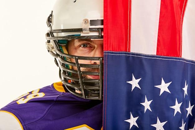 Spieler des amerikanischen fußballs auf hälfte schloss durch amerikanische flagge