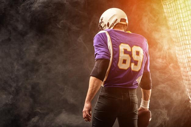 Spieler des amerikanischen fußballs, der ball in seinen händen hält