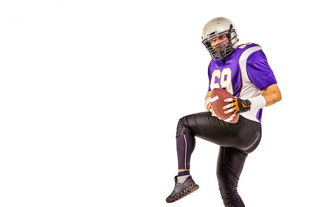 Spieler des amerikanischen fußballs, der mit ball auf schwarzem hintergrund aufwirft