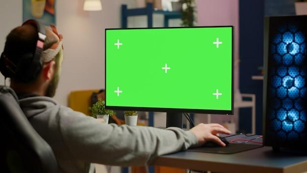Spieler, die videospiele auf einem leistungsstarken computer mit greenscreen-chroma-key-desktop-mock-up-anzeige im gaming-heimstudio spielen. spieler mit rgb-tastatur mit isoliertem monitor-streaming-spiel mit kopfhörer