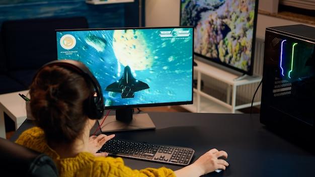 Spieler, die während der spielemeisterschaft spät in der nacht shooter-spiele mit anderen spielern spielen. pro esport-teamplayer-streamer während eines e-game-turniers auf einem leistungsstarken rgb-computer mit streaming-technologie