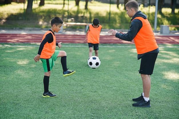 Spieler in fußballuniform, der den kickball mit trainer auf stadion ausarbeitet